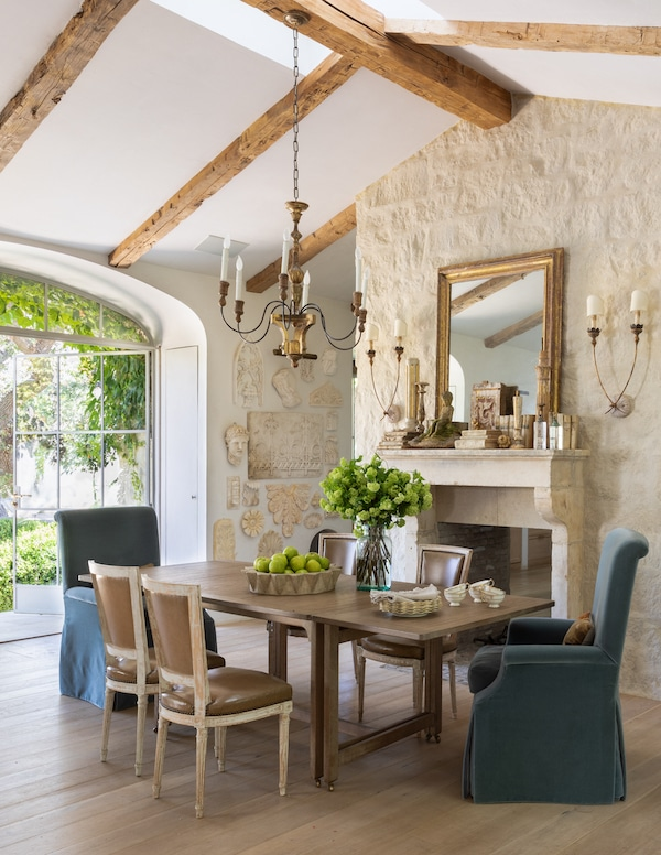 kitchen table of farmhouse with blue armchairs and wooden chairs