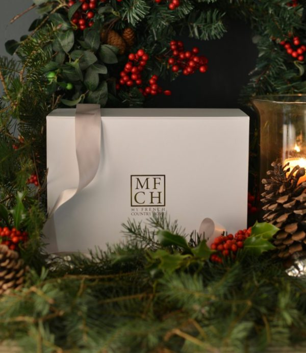 white subscription box with ribbon, holly, pine cones and pine branches