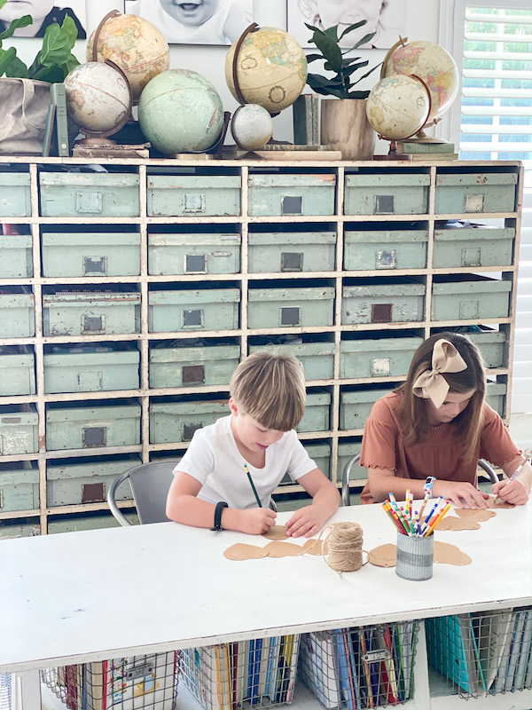 children writing at desk with storage