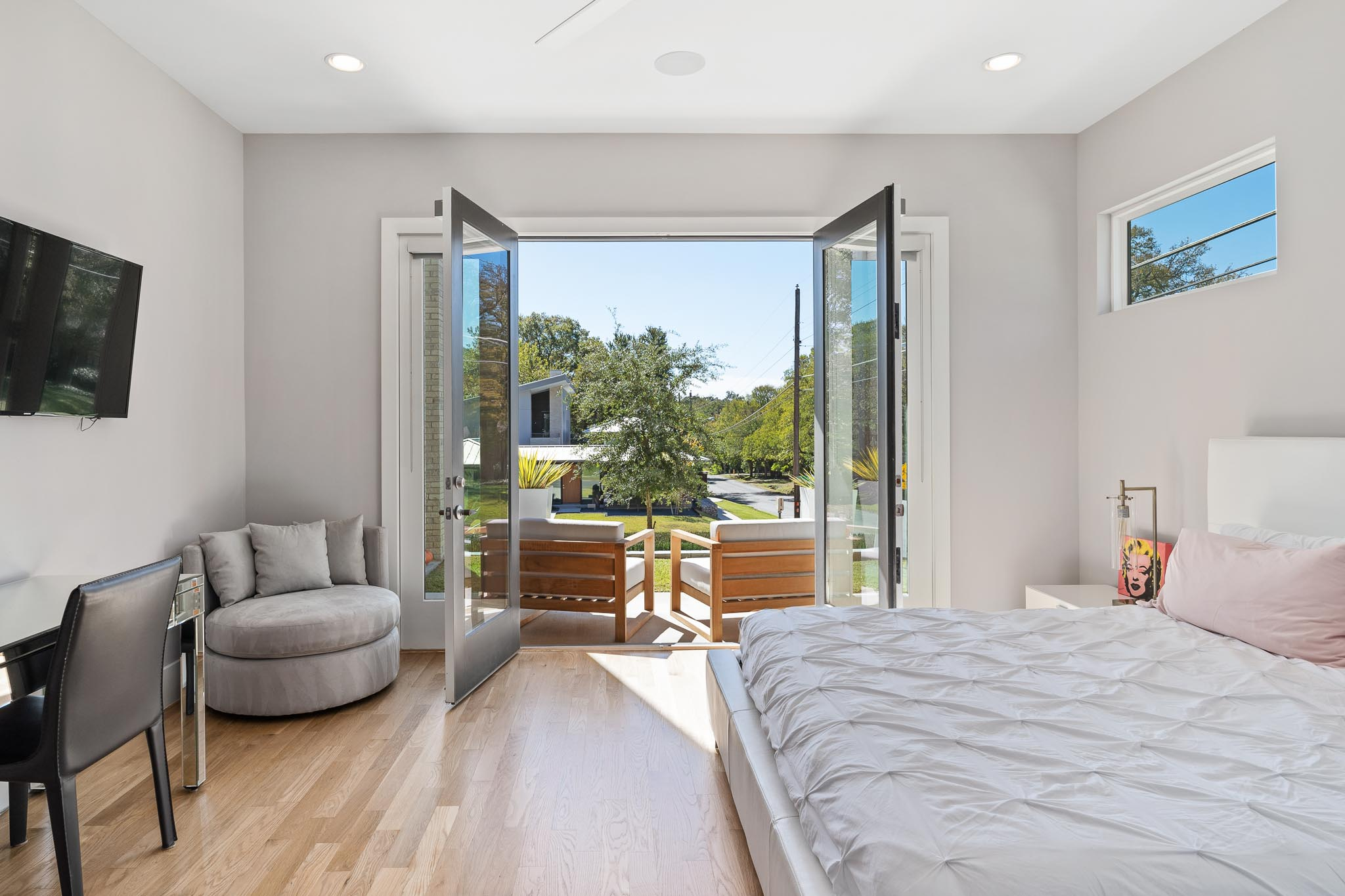 Large master suite with balcony and wood floors