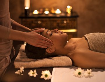 Young African American woman enjoying at the spa with her eyes closed while receiving head massage.
