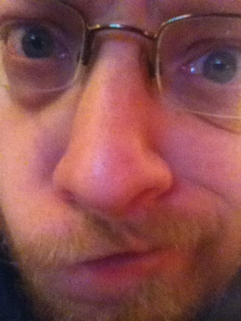 Four eyes, unkempt beard, big nose, smirk.