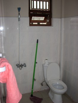 Here's our humble bathroom. Things to notice are the pink towel, the dyed-red mop, and the shower and the toilet only a few feet apart. Finally, I've been able to cut out the middle man while showering. For any plumbers out there, the floor drain is just behind the toilet.