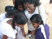 Matron shows off her pics to these local children.
