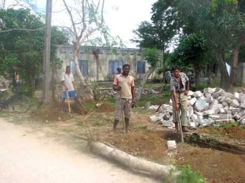 Men rebuilding in a residential area.