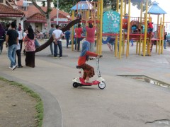 This little Malay girl was ruling the playground with her motorized scooter.