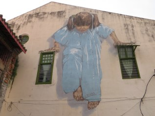 This is a giant mural of a little girl swinging from the windows.