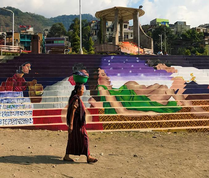 An indigenous woman passing through a mural in Santiago