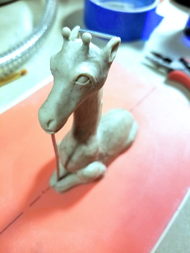 small clay giraffe sculpture with wire supports