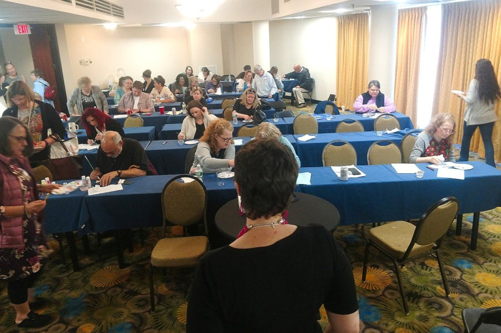 Adult woman standing at the front of a room with rows of tables and people seated at them in front of her