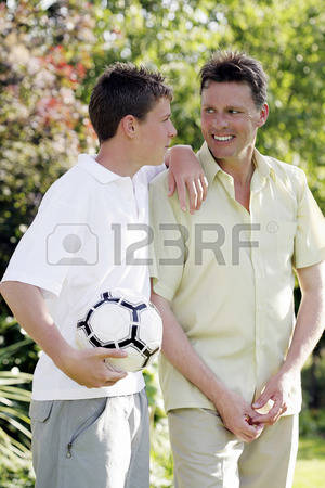 26204839-boy-holding-soccer-ball-while-talking-to-his-father