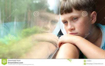 sad-boy-rides-train-sits-coupe-looks-out-window-57509567