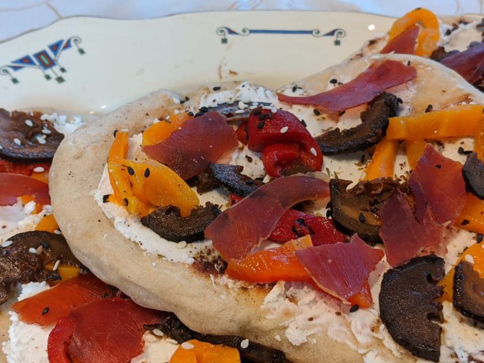 Plate of flatbreds with cheese, peppers, pickled walnuts
