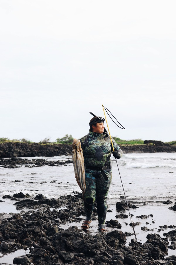 Woman standing on a rocky beach wearing diving gear and holding an octopus and net.