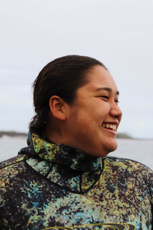 Close up portrait of a woman looking to the side and smiling, wearing diving gear on a rocky beach