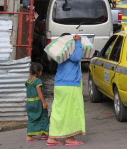 Indiofrau mit Tocher am Reisschleppen - die Frauen tragen alle eine farbenfrohe Tracht