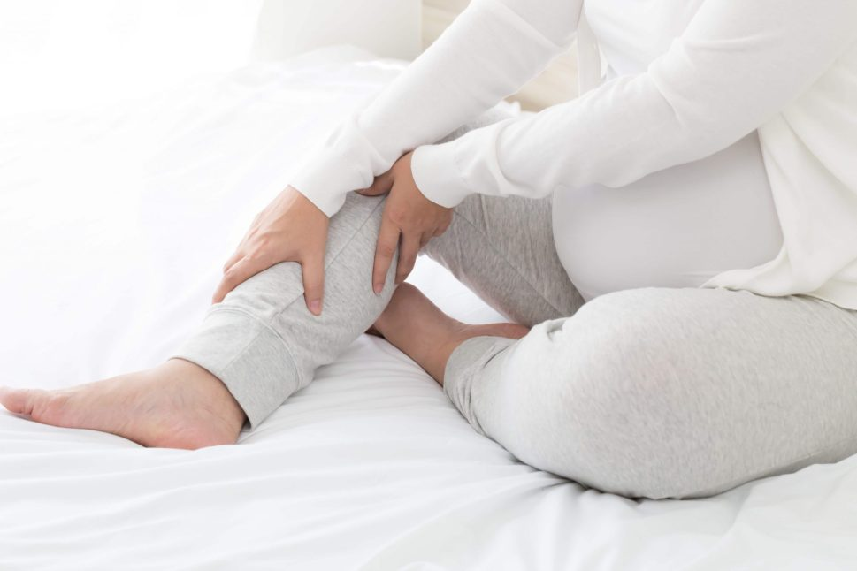 pregnant woman sitting on bed massaging leg cramp