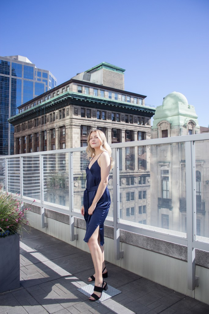 a blonde woman in a blue silk dress and black heels on a rooftop patio
