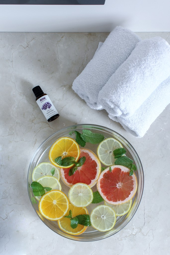Lavender oil, white towels, and citrus water placed on a countertop
