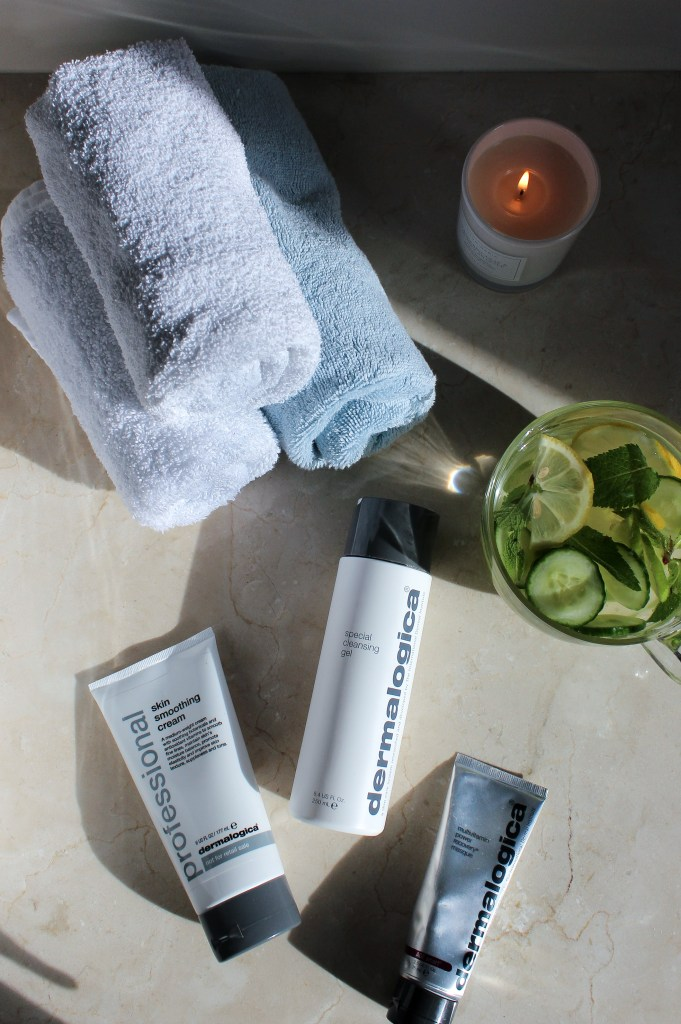 Skincare products laid out with towels, candle, and citrus water