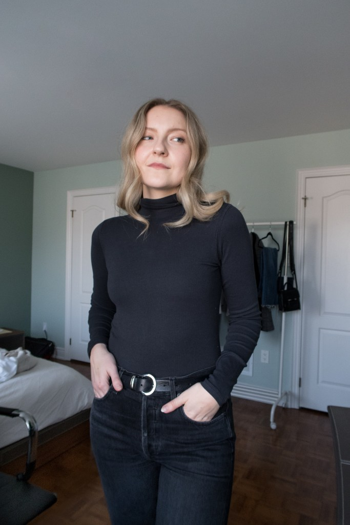 A blonde woman posing in a black turtleneck and black jeans