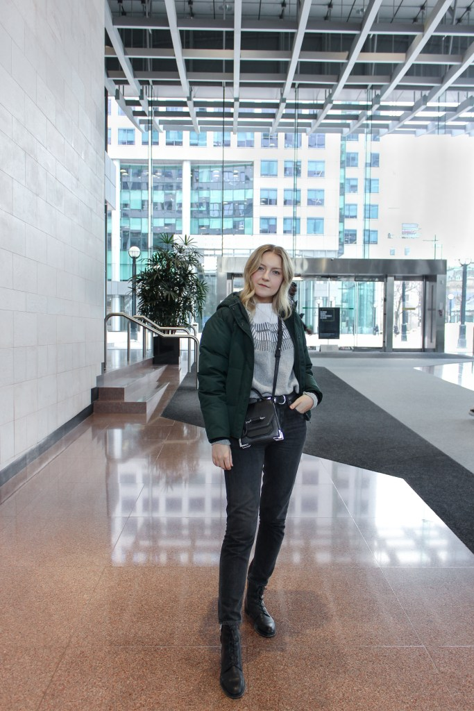 A blonde woman posing in an Everlane ski sweater, black denim, and a green puffer coat with a black crossbody bag inside an indoor building complex