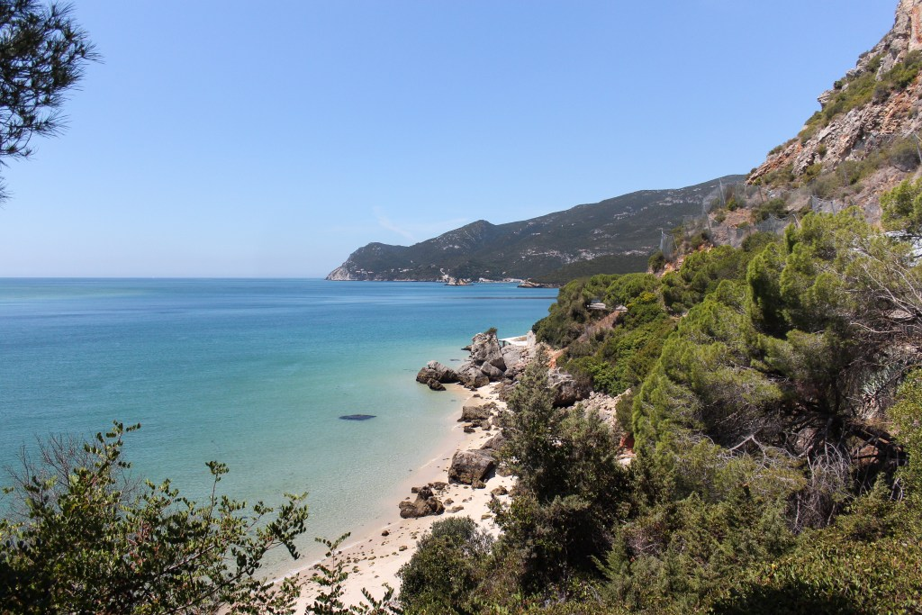 A viewpoint overlooking the beach and turquoise waters of the Arrábida Natural Park in Setubal