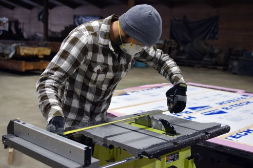 Setting the table saw width ro rip the rigid board insulation to the correct width.