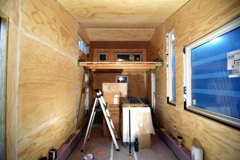 The kitchen has been moved to the center and covered in preparation for a day of sanding the spackled seams smooth.