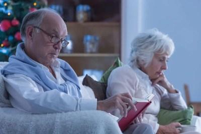 Sad elderly couple spending Christmas in a dark living room