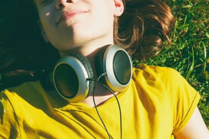 Woman lying in grass listening to healing music with headphones