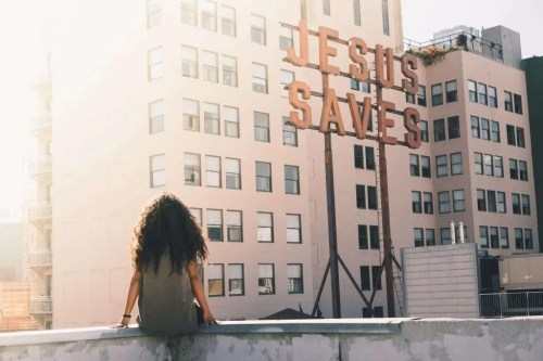 Woman looking at Jesus Saves sign in the city