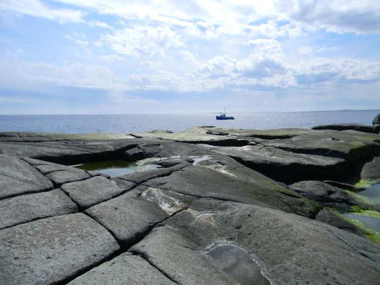 A granite shoreline with a fisherman's boat beyond.