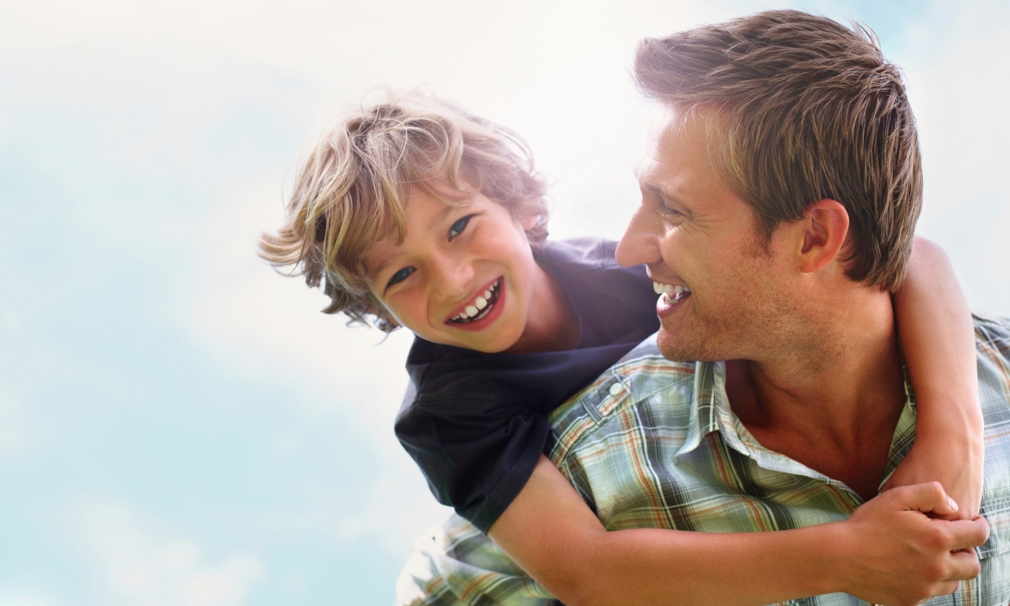 This image shows a son riding on his dad's back. It illustrates the need for adoptive and foster parents to celebrate adoption with their kids. Practical tips are offered here about ways to celebrate.