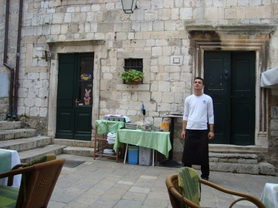 Waiter standing by the entrance to a cafe - Dubrovnik, Croatia