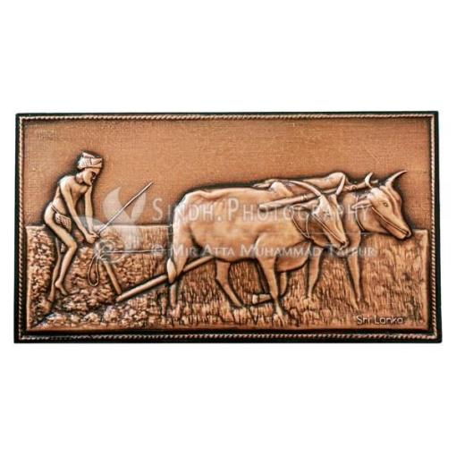 Ploughing farmer with bullocks - A copper plated wall hanging from Sri Lanka