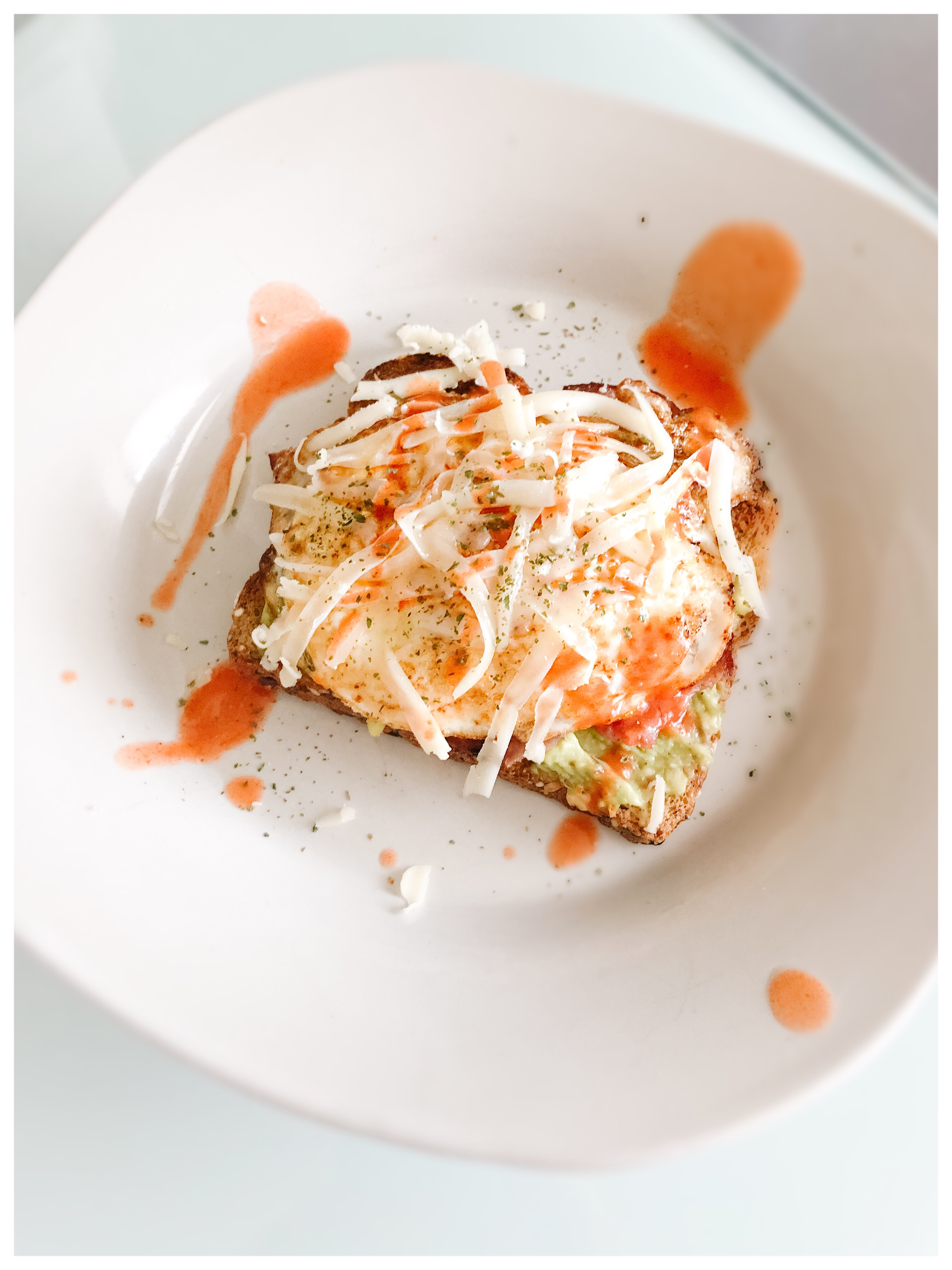 The Best Avocado Toast Recipe - ripe avocado mixed with olive oil, spices over hearty whole wheat toast with a fried egg and Frank's Red Hot sauce is the perfect weekend breakfast