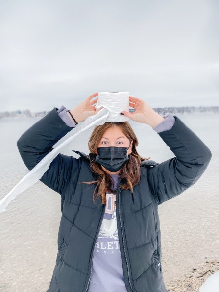 Woman wearing a mask and holding a roll of toilet paper on her head
