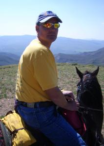 This i a photo of a middle-aged Caucasian man sitting on a black horse