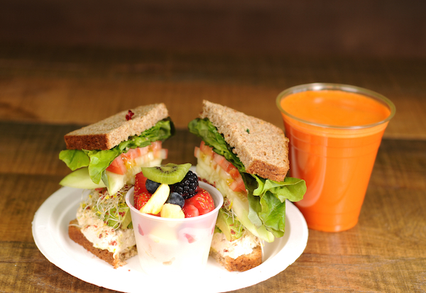 Jan's Tuna Avo Sandwich on a plate with fruit salad and carrot smoothie