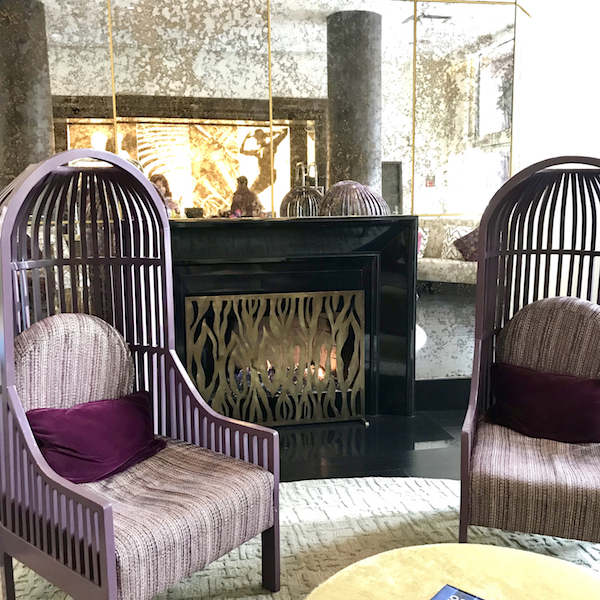 Purple bird cage chairs in front of Art Deco fireplace, Avenue of the Arts Hotel