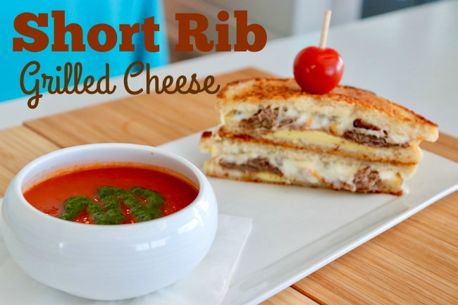 Short Rib Grilled Cheese and Tomato Soup with pesto on a white plate