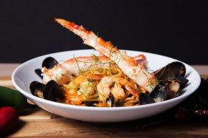 Seafood Pasta of clams, mussels, shrimp, spaghetti, spicy tomato sauce in a white bowl