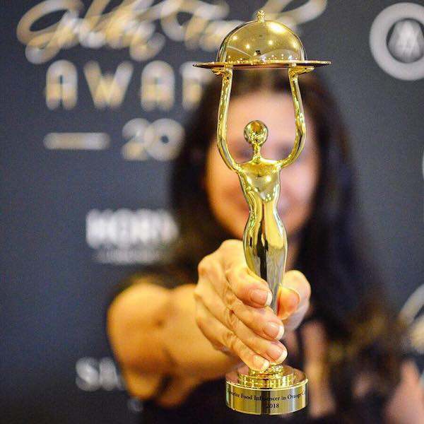 Connie Aboubakare holding up her Golden Foodie award