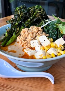 Bowl of vegan ramen with sesame miso broth, broccolini, tofu, bean sprouts, soy meat, chili oil