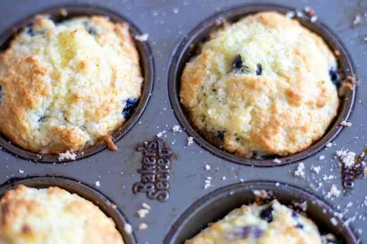 cooked lemon blueberry muffins in muffin tin