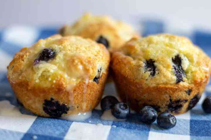 three lemon blueberry muffins sitting on blue and white napkin