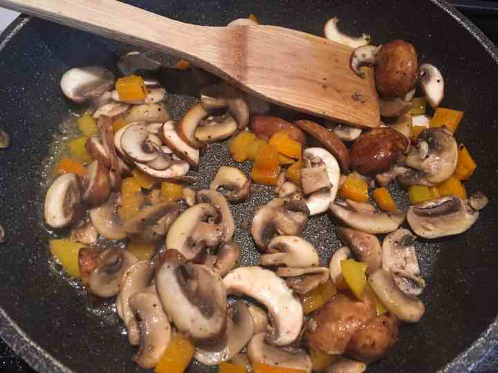 mushrooms yellow orange peppers in frying pan with wooden spoon