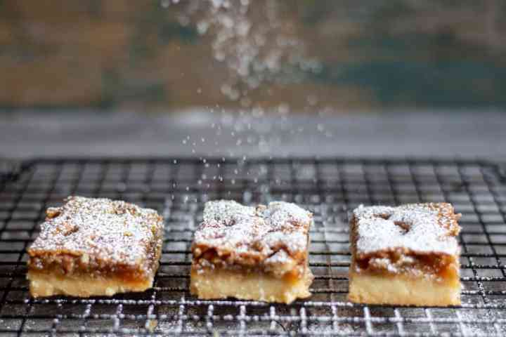 3 pecan butter tart squares on wire cooling rack with icing sugar dusting from above