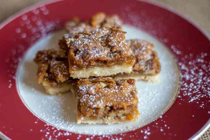 five pecan butter tart squares on red and white plate with a light dusting of icing sugar